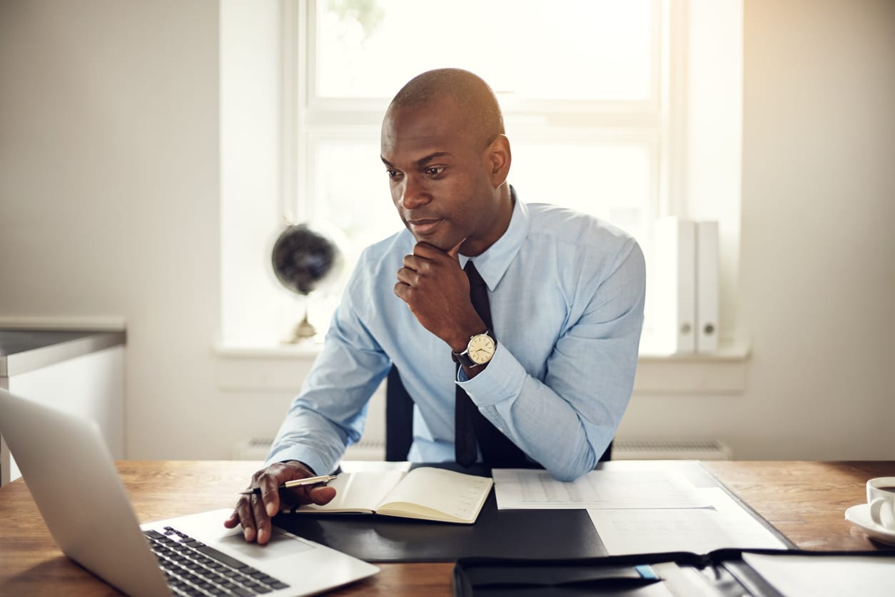 man in professional clothing sitting at desk with laptop